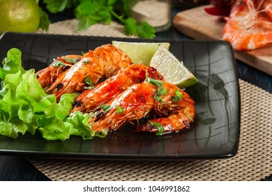 Shrimps roasted with onion, garlic and chili served on black plate.