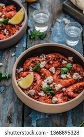 Shrimps saganaki with feta cheese on a plate on a table