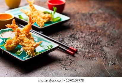 Shrimps tempura with spicy chili sauce on blue plate.  Seafood tempura dish of traditional asian cuisine .