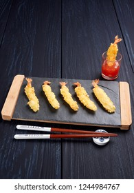 Shrimps tempura with sweet chili sauce on black slate board, set on a dark blue background