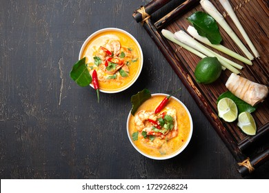 Shrimps Tom Yam Kung in white bowls, top view, wooden background
