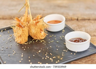 Shrimps wrapped in kataifi dough on plate. Appetizing fried shrimps in dough kataifi served with sauce on black plate. Crispy appetizer in restaurant.