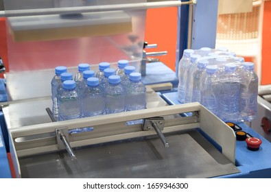 Shrink film wrapping machine for package bottle of water. Food industry