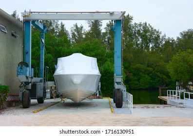 Shrink wrapped boat strapped on a mobile lift preparing it for winter storage, shipment or launching with a boat ramp and waterway canal in the background with many green trees.