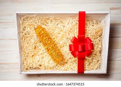 Ein schrumpfender Trockenmaiskolben in der Geschenkbox. Unsinniges Missachtungsgeschenk.Konzeptuelles Foto.