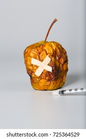 Shriveled apple and insulin ultra thin syringe on a gray surface. Closeup