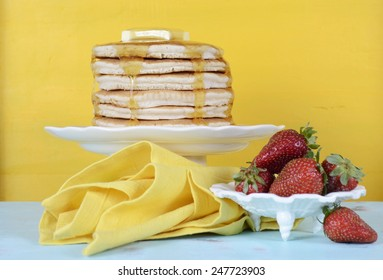 Shrove Pancake Tuesday stack of pancakes with honey and butter and strawberries on yellow and aqua blue vintage shabby chic table.