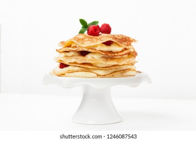 Shrove tide idea, pancake cake with raspberries, white background