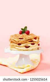 Shrove tide idea, pancake cake with raspberries, pink background