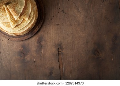 Shrovetide Maslenitsa Butter Week festival meal. Stack of russian pancake blini on a dark rustic wooden background. Top view with copy space