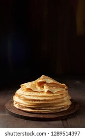 Shrovetide Maslenitsa Butter Week festival meal. Stack of russian pancake blini on a dark rustic wooden background. Front view with copy space