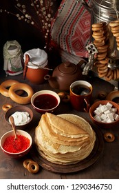 Shrovetide Maslenitsa Butter Week festival meal. Stack of russian pancakes blini with red caviar, fresh sour cream and cranberry jam on the background of samovar. Rustic style, close up view