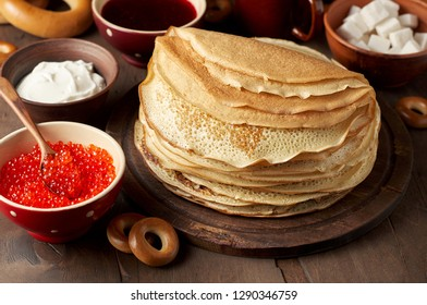 Shrovetide Maslenitsa Butter Week festival meal. Stack of russian pancakes blini with red caviar, fresh sour cream and cranberry jam. Rustic style, close up view