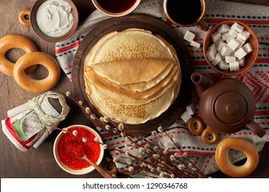 Shrovetide Maslenitsa Butter Week festival meal. Stack of russian pancakes blini with red caviar, fresh sour cream, cranberry jam and sushki. Rustic style, close up top view