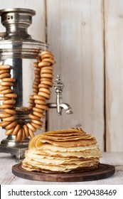 Shrovetide Maslenitsa Butter Week festival meal. Stack of russian pancakes blini on the background of samovar with sushkie. Rustic style, close up view with copy space