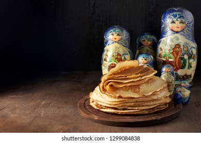 Shrovetide Maslenitsa Butter Week festival meal. Stack of russian pancakes blini and traditional wooden dolls matrioshka. Rustic style, close up view with copy space