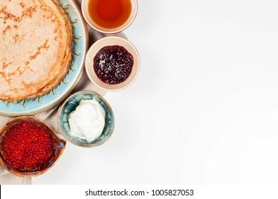 Shrovetide Maslenitsa festival meal. Russian pancake blini with raspberry jam, honey, fresh cream and red caviar on white background