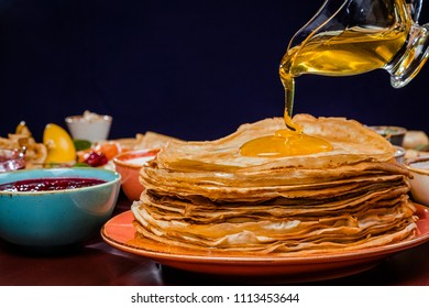Shrovetide Maslenitsa festival meal. Russian pancakes blini with honey, fresh cream cheese and red caviar. Rustic style