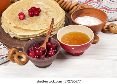 Shrovetide Maslenitsa festival meal. Russian pancake blini with cranberry, honey, fresh cream and red caviar on white wooden background