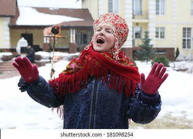 shrovetide party, woman in national costume singin on the winter mansion background