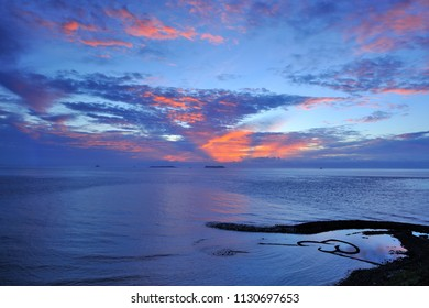 Shuang xin Shi Hu is a famous tourist attraction in Taiwan Penghu, the blue Sea reflects the sky Red Cloud is very beautiful, silhouette is a double heart stone-Shanghai figure.