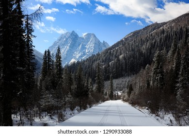 ShuangQiao Valley Scenic Area, Four Girls Mountain National Park in Sichuan Province China. Snow Capped Jagged Mountains and Blue Sky, Snow Mountains, Empty National Park Utility Access Road