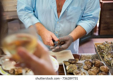 Shucking fresh oysters with an oyster knife on a fish market. People with a glass of champagne or sparkling wine