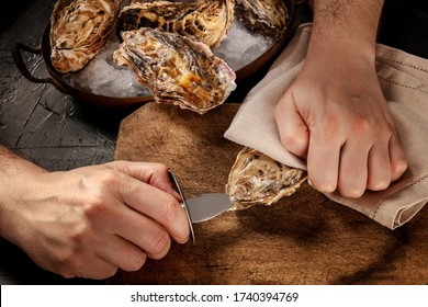 Shucking an oyster, man's hands with a special knife, opening oysters on a wooden board