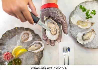 shucking an oyster as water drips out. The oyster opening is in focus and the person hands with oyster plate background.