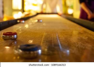 Shuffleboard game in progress, night, interior.