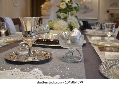 A Shulchan Aruch for the Pesach passover Seder meal, which is being conducted by ultra-Orthodox and religious Jews with a seder bowl, a cup of cups and plates and ornaments
