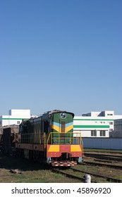 Shunting loco on railroad. On background new plant