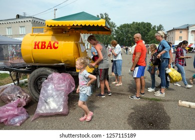 """SHUSHENSKOE, Krasnoyarsk Territory/ RF - July 14,2018: Tourists buy kvass on the street of the village for the time of the annual Intl festival of music and crafts """"World of Siberia""""(FestMirSibiri)."""