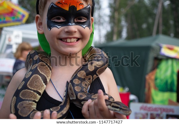 Shushenskoe, Russia- circa July 2018: Child with the picture on the face of batman holding in the hands of the snake on ethno festival the World of Siberia