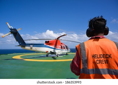 Shut down helicopter with helipad crew on jack up oil rig helipad with blue sky
