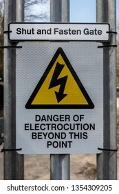 Shut and fasten gate danger of electrocution beyond this point sign on a railway access gate in the United Kingdom
