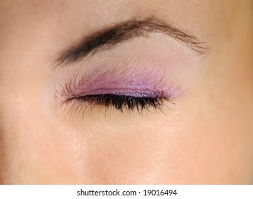 A shut feminine eye, horizontal, with makeup