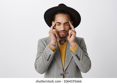 Shut up, give me time to concentrate. Bothered good-looking dark-skinned creative entrepreneur in fashionable outfit, closing eyes, holding fingers on temples, feeling headache or trying focus