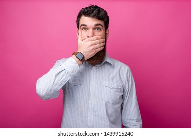 Shut your mouth! Man in casual covering mouth with hand