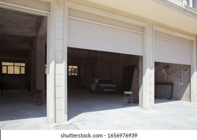 Shutter door or roller door and concrete floor outside .White Automatic shutters in a house . gates in the garage . Automatic Electric Roll-up Gate Or Push-up Door In The Modern Building Ground Floor