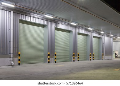 Shutter door or roller door and concrete pavement floor outside factory building for industry background.