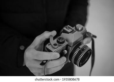 Shutter release on a Retro vintage Praktica ltl SLR film camera in a leather case and a 50 mm 2.8 Carl Zeiss Jena lens. Retro toning. (March 14, 2021, Uzhgorod, Ukraine)