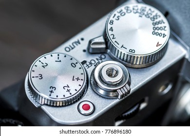 Shutter speed and exposure control dial, button, on silver modern mirrorless camera, Soft Focus.
