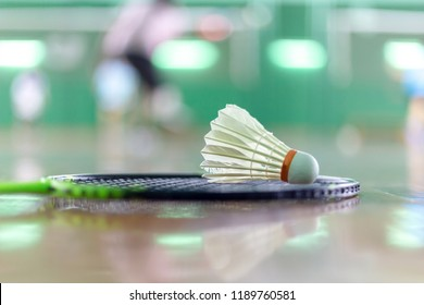 Shuttercock on badminton racket with blurred background
