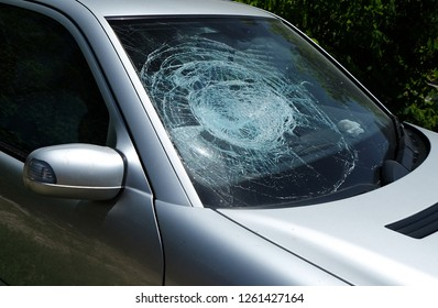 Shuttered cracked broken damaged crashed car windshield at the right passenger side after a car accident. Dangerous, careless, unsafe, drunk, impaired  driving, DUI, car crash injury fatality concept.