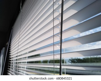 Shutters or Jalousie louvers or wooden blinds in backlight flowing from window in sunny day. Abstract black and white interior photograph.