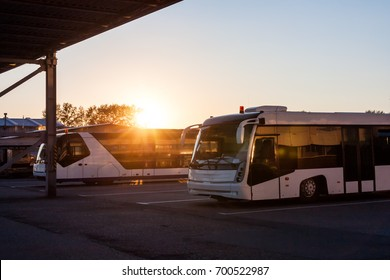 Shuttle buses at the parking lot of the airport in the rays of the setting sun