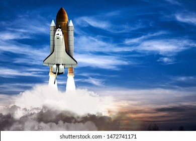 A shuttle spaceship taking off on background of blue night cloudy sky.