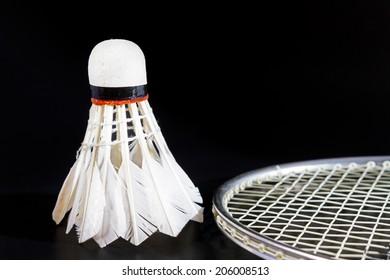 Shuttlecock and badminton on dark background