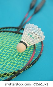 Shuttlecock and badminton racket on blue background